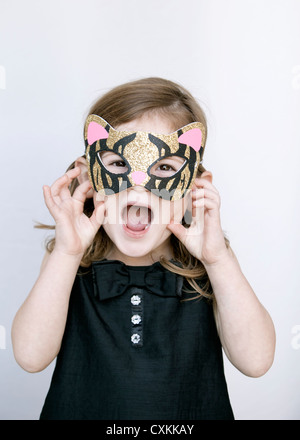 Little girl with tiger mask - Stock Photo