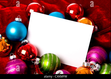 A group of colorful Christmas baubles or ball surrounding a white notecard with copy space - Stock Photo