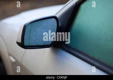 Icy car in winter, ice on the rearview mirror and on the windows - Stock Photo