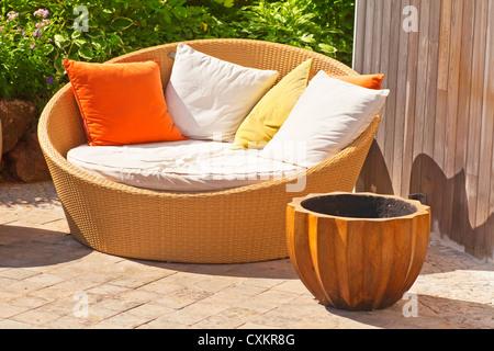 A modern wicker garden sofa or love seat in the home garden. - Stock Photo