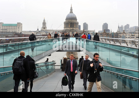 Commuters make their way to work on Millennium Bridge, London, UK - Stock Photo