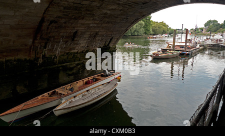 River Thames view of boats and people boating on water seen through bridge tunnel in Richmond upon Thames, London, - Stock Photo