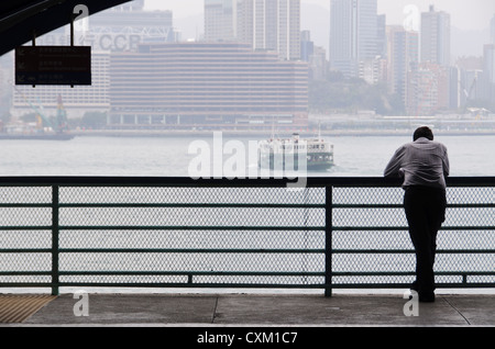 Man overlooking Victoria Harbour from Wan Chai ferry pier, Hong Kong Island, as the iconic Star Ferry sails across. - Stock Photo