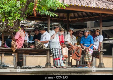 Men at a communial meeting place, in the Bali Aga village of Tenganan, near Candi Dasa, Eastern Bali, Indonesia. - Stock Photo