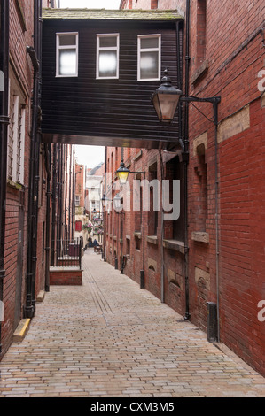 View down narrow enclosed alleyway, lined with high brick walls & glass lanterns to historic inn - Ship Yard, Leeds - Stock Photo