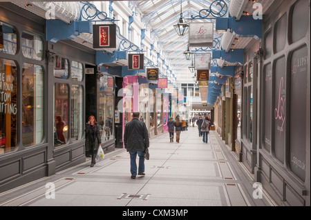 Shoppers walking in attractive historic Queen's Arcade (rows of shops under impressive glass roof) - Leeds city - Stock Photo