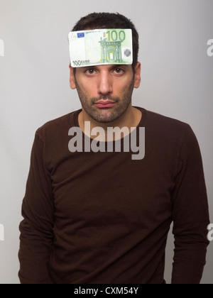 Portrait of sad looking young man with 100 euro bill on forehead - Stock Photo