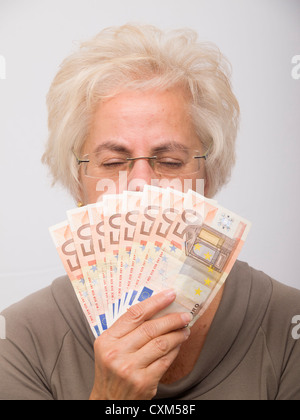 Mature woman holding money (euro bills) - Stock Photo