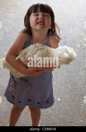Excited young girl proudly holding her White crested buff polish chicken at Monroe County fair, rural Indiana, America. - Stock Photo