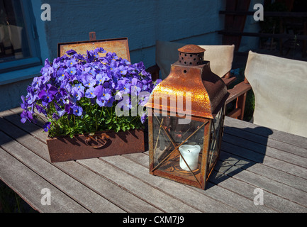 Rusty chest with purple flowers and lamp on wooden table in 'Old Town' Helsinki, Finland - Stock Photo