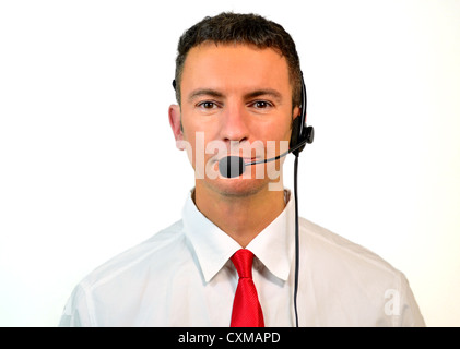 Good looking young man, at sales or support department, with headset - Stock Photo