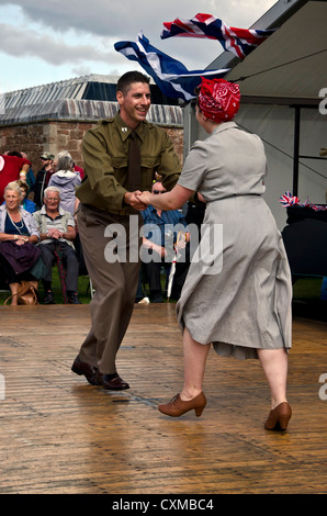 Couple in WW2 period clothes dancing the jitterbug at an historic event at Fort George near Inverness, Scotland. - Stock Photo