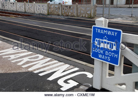 Warning signs, including tram icon, for pedestrians at a tramway crossing in Blackpool, Lancashire, UK - Stock Photo