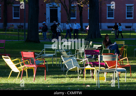 Colorful chairs wait for weary students and tourists alike, in the sun in Harvard Yard, the old heart of Harvard - Stock Photo