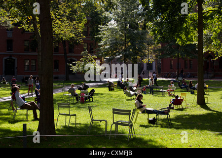 Tourists and students rest in lawn chairs on a sunny afternoon in Harvard Yard, the old heart of Harvard University - Stock Photo