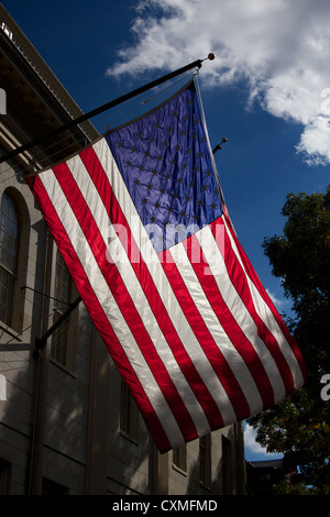 United States flag waving over the John Harvard Statue in Harvard Yard, the old heart of Harvard University campus - Stock Photo