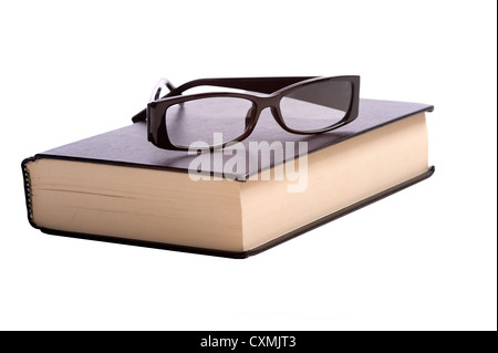 A pair of fashionable reading glasses on top of a black book on a white background with copy space - Stock Photo