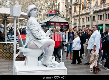 Mime on Las Ramblas in Barcelona sitting on toilet reading newspaper - Stock Photo