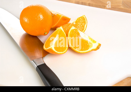 Freshly cut oranges with knife on white cutting board - Stock Photo