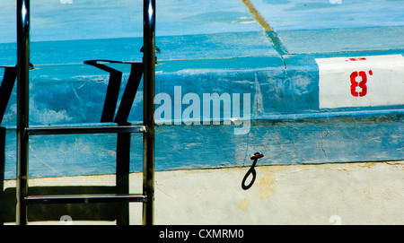 old, empty swimming pool with ladder abstraction - illustration of 'summer's over' or 'the best is past' - Stock Photo