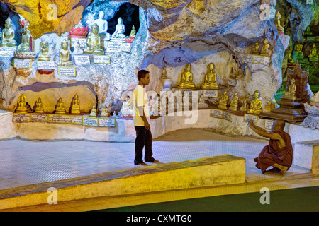 Buddhist Monk Photographing a Friend in the Shwe Oo Min Cave, Pindaya, Shan State, Myanmar, Burma. - Stock Photo