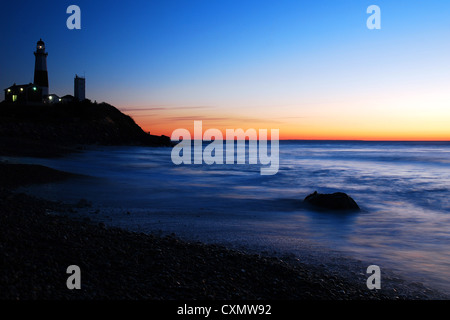 Dawn breaks on the lighthouse at Montauk Point - Stock Photo