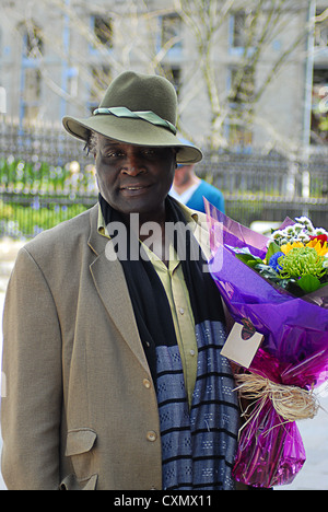 Black man in best clothes carrying a bouquet of flowers - Stock Photo