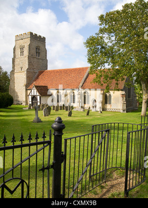 An old English church pictured with a wrought iron kissing gate and fence in the foreground. - Stock Photo