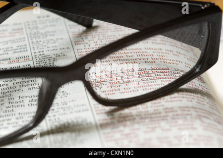 A pair of reading glasses on top of a a Bible open to John 3, religious study - Stock Photo
