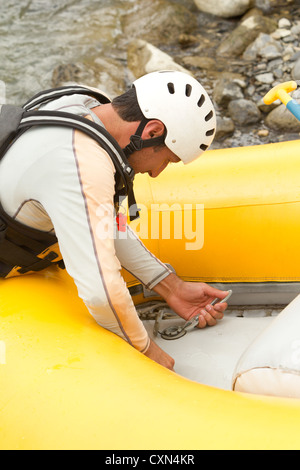 Rafting Boat Maintenance The Pilot Preparing The Boat For The Next Adventure - Stock Photo