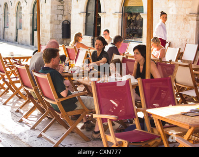 Families and couples eating outdoors,  having snacks at Dubrovnik street cafe. - Stock Photo
