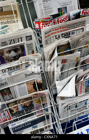 A rack of foreign newspapers for sale in Central London. - Stock Photo