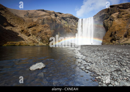 The stunning Skogafoss waterfall in Iceland, with person dwarfed underneath a colourful waterfall - Stock Photo