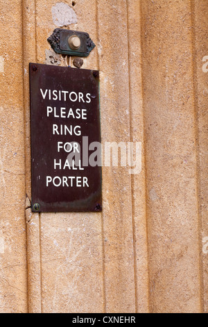 'Visitors please ring for hall porter' sign by door bell button. - Stock Photo