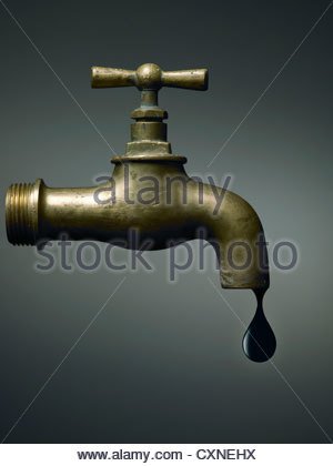 Old tap with the last oil drop, abstract on dramatic background - Stock Photo