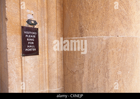 'Visitors please ring for hall porter' sign by door bell button - Stock Photo