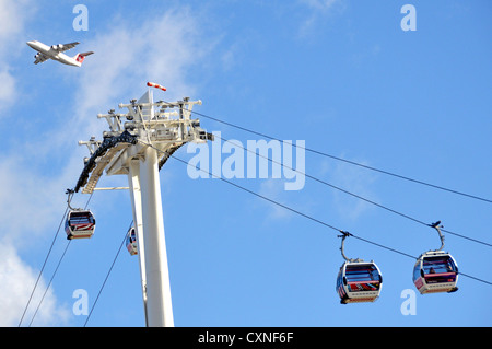 Swiss International Air Lines passenger jet on take off from London City Airport flying above top of cable cars - Stock Photo