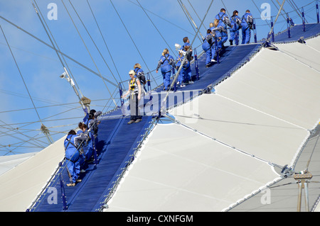 Up At The O2, people kitted out in blue overalls walking on roof of the o2 arena, sometimes referred to as the Skywalk - Stock Photo