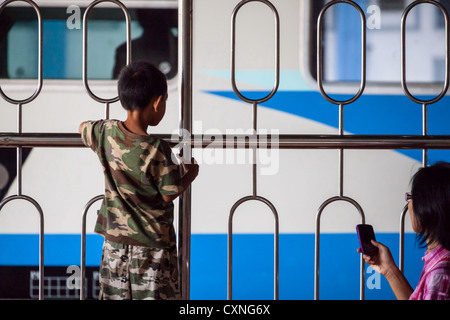 Little Boy looking at a Train at the Railway Station in Yogyakarta in Indonesia - Stock Photo
