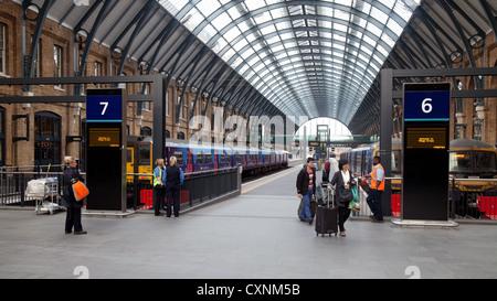 Rail passengers arriving at Kings Cross railway train station, London UK - Stock Photo