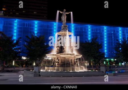 Tyler Davidson Genius of Water Fountain in Fountain Square, Cincinnati at night with blue illuminated building - Stock Photo