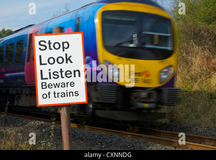 Speeding train and sign, by pedestrian crossing over railway line, warning people about trains - Stock Photo