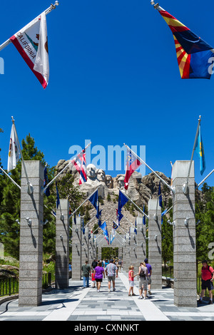 Tourists at Mount Rushmore National Memorial with avenue of state flags leading to viewing area, Black Hills, South - Stock Photo