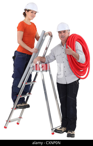 female plumber on ladder with male tutor - Stock Photo