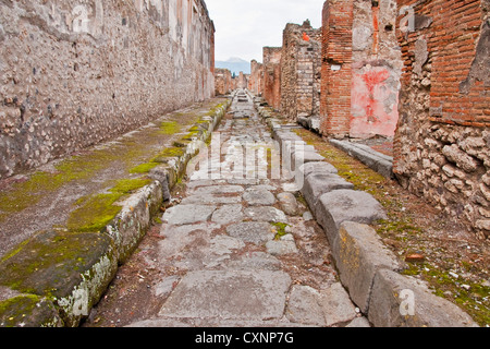 Ancient Roman city of Pompeii, narrow paved stone side street and building ruins - Stock Photo