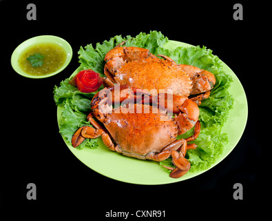 Steamed crabs a great tasty seafood display on dish isolated on black background - Stock Photo
