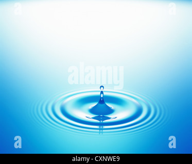 Drop of Water Spreading Ripples - Stock Photo
