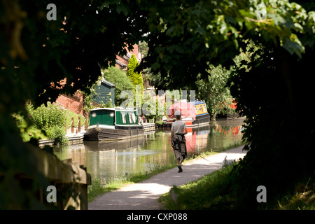 A woman walks her dog along the Fazeley canal in Tamworth, Staffordshire. Pictured here the stretch of canal behind - Stock Photo