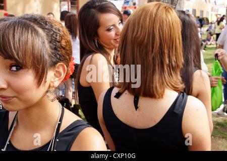 hispanic latino teen teenager girl looking at camera suspicious glance glancing crowd girls outcast shunned - Stock Photo