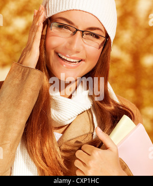 Photo of beautiful happy student girl holding textbook, closeup portrait of young stylish businesswoman wearing - Stock Photo